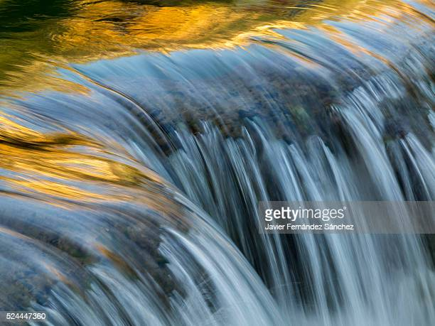 A golden reflections in the water from a waterfall.