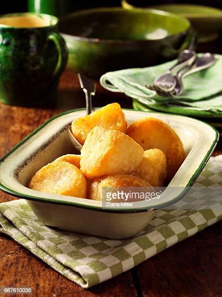 Golden roast potatoes in vintage dish, wooden table