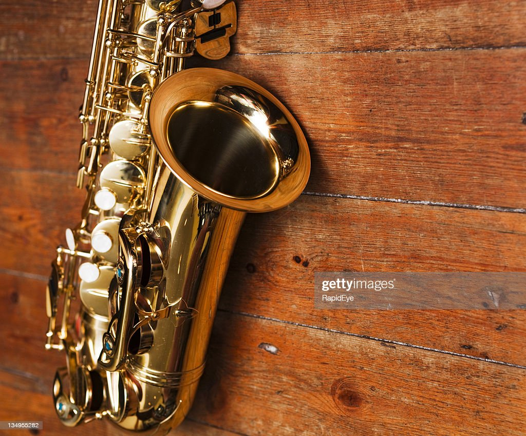 Golden sax against heavily grained wood : Stock Photo