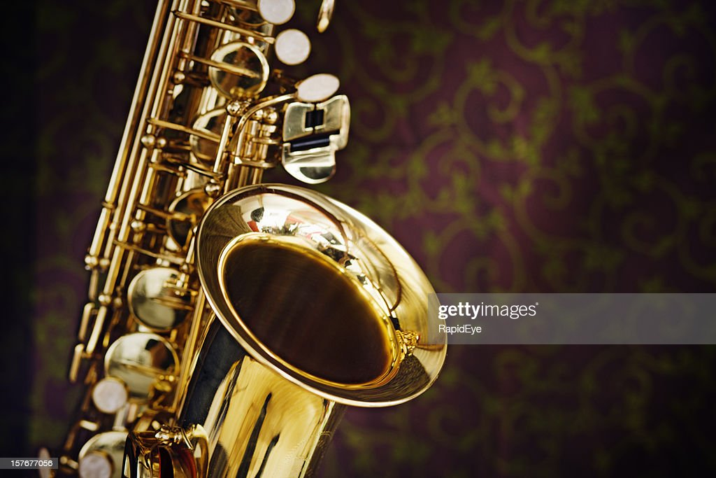 Golden saxophone gleams against a background of richly figured silk : Stock Photo