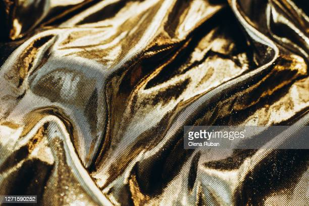 golden shiny fabric beautifully crumpled - modeshow stockfoto's en -beelden