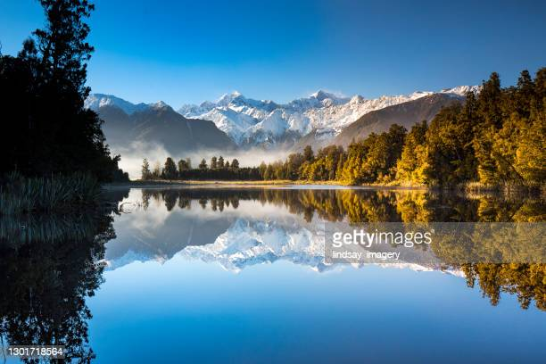 golden snow capped mountain range reflecting perfectly on mirror lake with bright blue sky - snowcapped mountain stock pictures, royalty-free photos & images