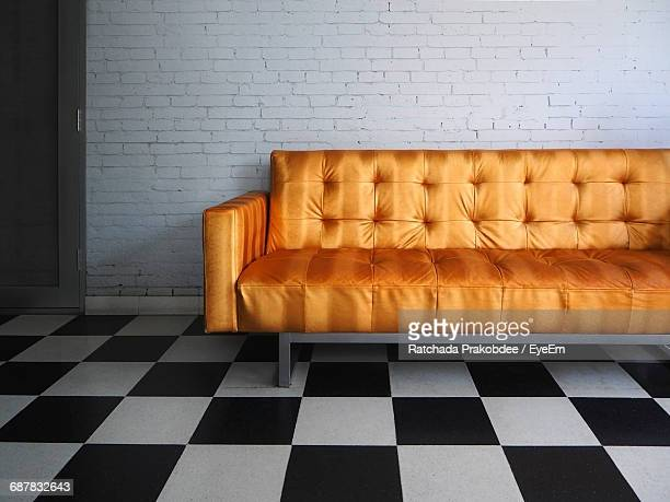 Golden Sofa On Tiled Floor Against Brick Wall At Home