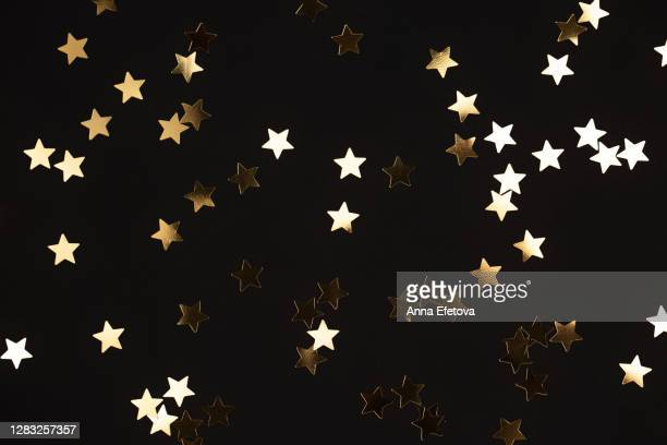 golden star shaped confetti during party - star shape stock pictures, royalty-free photos & images