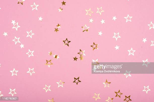 golden stars glitter on pink background. festive holiday pastel backdrop. - star shape stock pictures, royalty-free photos & images