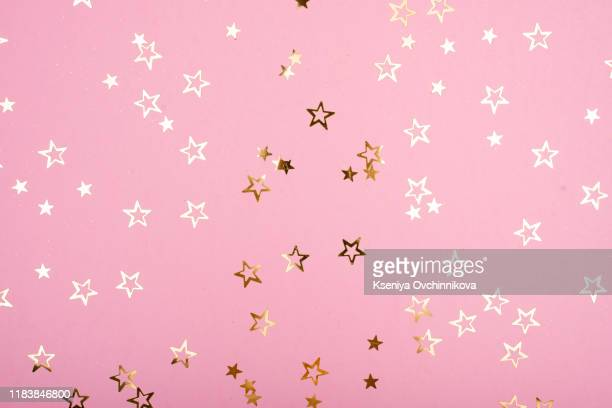 golden stars glitter on pink background. festive holiday pastel backdrop. - pink sparkles stock pictures, royalty-free photos & images
