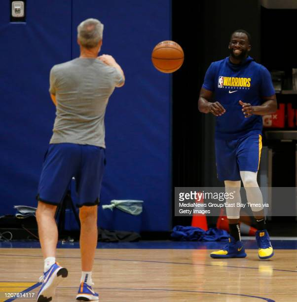 Golden State Warriors assistant coach Bruce Fraser throws a ball to Draymond Green during practice at the Biofreeze Performance Center in San...