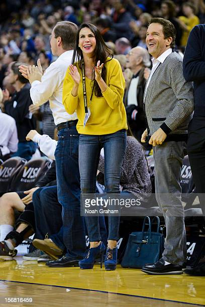 Golden State Warriors co-owners Joe Lacob, left, and Peter Guber, right, along with Lacob's fiancee Nicole Curran, cheer on the team during a game...