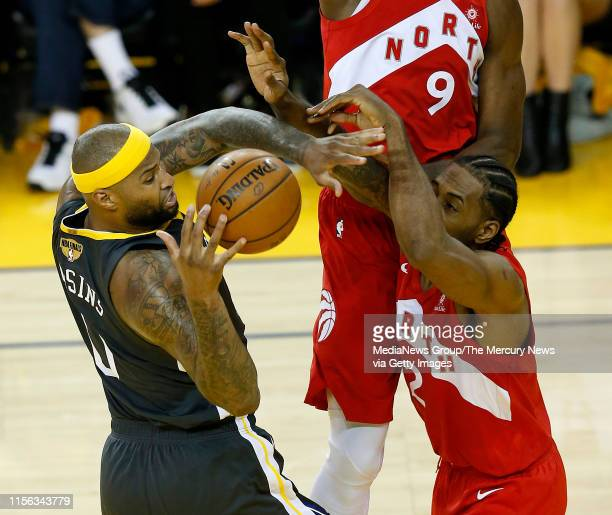 JUNE 13 Golden State Warriors' DeMarcus Cousins looses control of the ball as he's guarded by Toronto Raptors' Kawhi Leonard during the fourth...