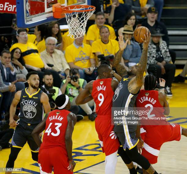 JUNE 13 Golden State Warriors' DeMarcus Cousins shoots past Toronto Raptors' Serge Ibaka and Kawhi Leonard during the first quarter of Game 6 of the...