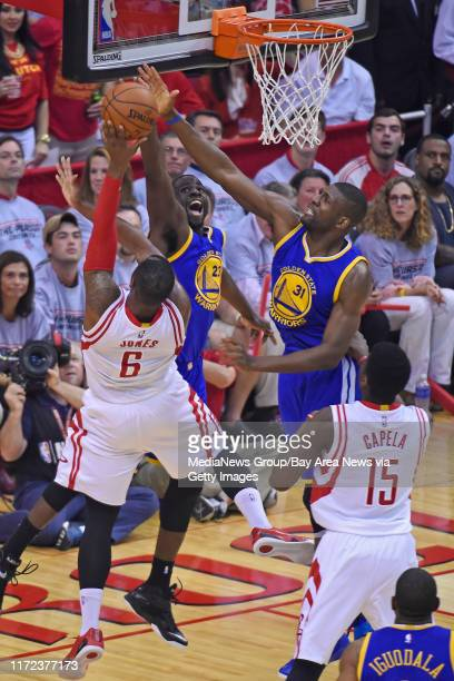Golden State Warriors' Draymond Green and Golden State Warriors' Festus Ezeli guard Houston Rockets' Terrence Jones while attempting to make a basket...