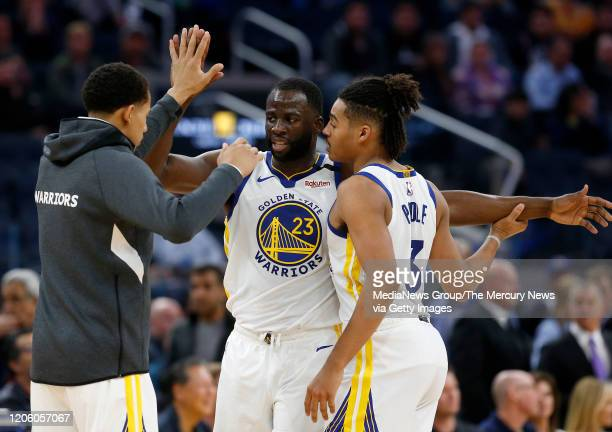 Golden State Warriors' Draymond Green celebrates a basket with Jordan Poole and Juan ToscanoAnderson in the third quarter of their NBA game at the...
