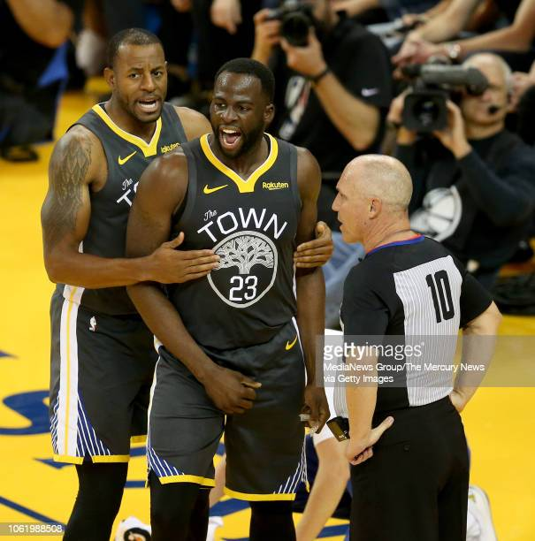 Golden State Warriors' Draymond Green disputes a foul called on him as he's held back by Andre Iguodala in the fourth quarter of their NBA game...