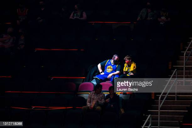 Golden State Warriors fans are illuminated by a spotlight before the start of the game against the Cleveland Cavaliers at Rocket Mortgage Fieldhouse...