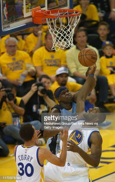 Golden State Warriors' Festus Ezeli and Memphis Grizzlies' Zach Randolph fight for a rebound as Golden State Warriors guard Stephen Curry looks on in...