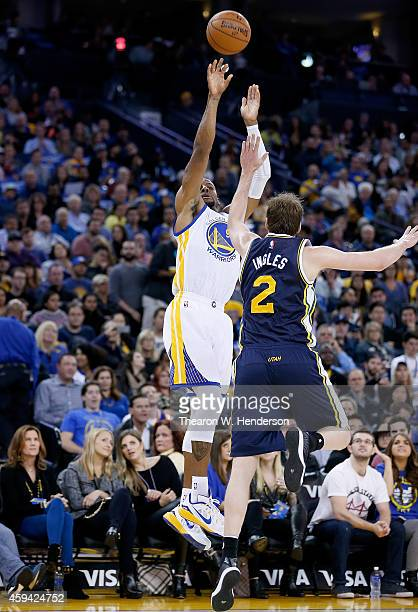 Golden State Warriors guard Andre Iguodala shoots over Utah Jazz forward Joe Ingles at ORACLE Arena on November 21, 2014 in Oakland, California.