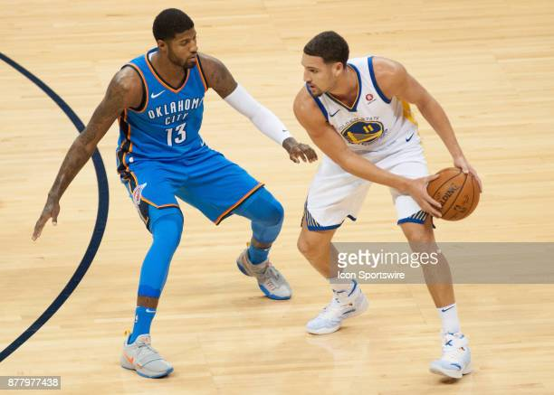 Golden State Warriors Guard Klay Thompson looks to pass while Oklahoma City Thunder Forward Paul George plays defense at the Chesapeake Energy Arena...