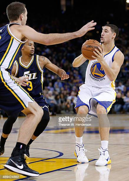 Golden State Warriors guard Klay Thompson looks to shoot on Utah Jazz guard Trey Burke and forward Steve Novak at ORACLE Arena on November 21 2014 in...