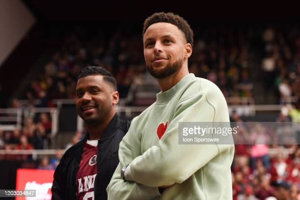 Golden State Warriors guard Stephen Curry and Seattle Seahawks quarterback Russell Wilson during the NCAA women's basketball game between the Oregon...