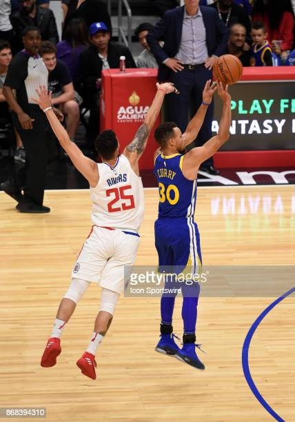 Golden State Warriors Guard Stephen Curry attempts a three pointer around Los Angeles Clippers Guard Austin Rivers during an NBA game between the...