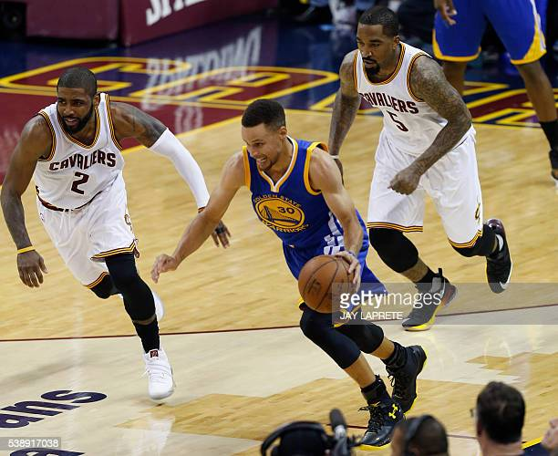Golden State Warriors guard Stephen Curry brings the ball up court against Cleveland Cavaliers guard Kyrie Irving and guard JR Smith during Game 3 of...