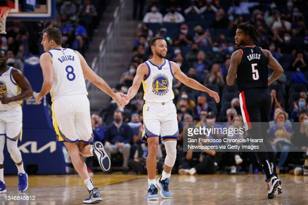 Golden State Warriors guard Stephen Curry celebrates the three-point field goal by Warriors forward Nemanja Bjelica in the first half of an NBA game...