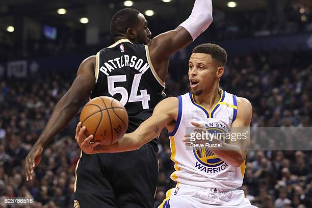 TORONTO ON NOVEMBER 16 Golden State Warriors guard Stephen Curry dishes off a pass behind Toronto Raptors forward Patrick Patterson as the Toronto...