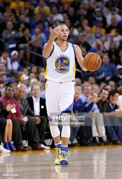 Golden State Warriors guard Stephen Curry dribbles the ball up court against the Utah Jazz at ORACLE Arena on November 21 2014 in Oakland California