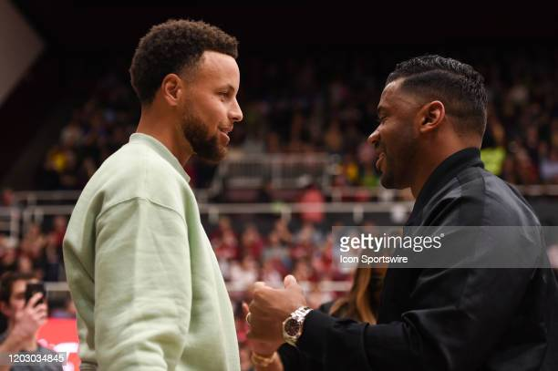 Golden State Warriors guard Stephen Curry in conversation with Seattle Seahawks quarterback Russell Wilson during the NCAA women's basketball game...