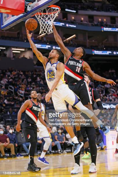 Golden State Warriors guard Stephen Curry is fouled after attempting a layup in the first half of an NBA game against the Portland Trail Blazers at...