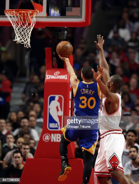Golden State Warriors guard Stephen Curry lofts a shot as Chicago Bulls forward Cristiano Felicio looks on during the first half on Thursday March 2...