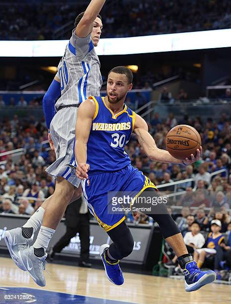 Golden State Warriors guard Stephen Curry looks to pass under Orlando Magic forward Aaron Gordon on Sunday Jan 22 2017 at the Amway Center in Orlando...
