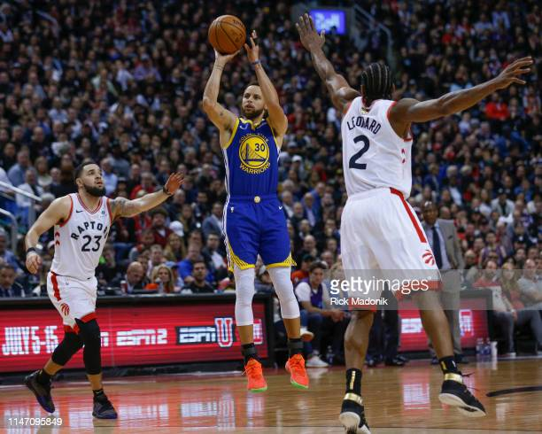 Golden State Warriors guard Stephen Curry pouts up a shot as Toronto Raptors guard Fred VanVleet and Toronto Raptors forward Kawhi Leonard converge....