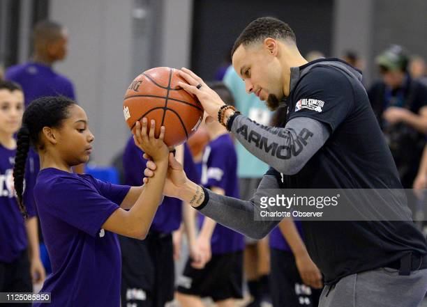 Golden State Warriors guard Stephen Curry, right, helps a student with positioning the ball for a shot during the Fourth Annual Jr. NBA Day at the...