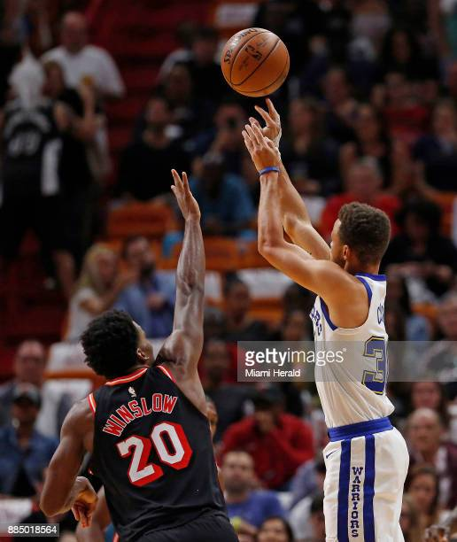 Golden State Warriors guard Stephen Curry shoots over Miami Heat forward Justise Winslow during the first quarter on Sunday Dec 3 2017 at...