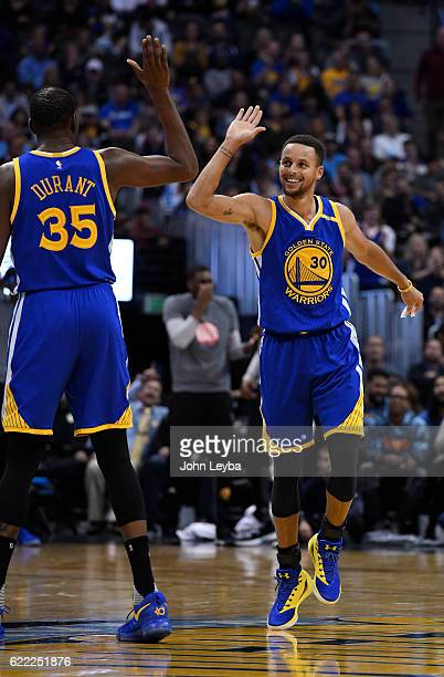 Golden State Warriors guard Stephen Curry smiles and high fives Golden State Warriors forward Kevin Durant after hitting a three pointer and getting...