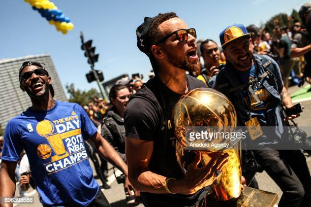 Golden State Warriors' Ian Clark and Stephen Curry carry the Larry O'Brien Trophy during the Golden State Warriors' NBA Championship parade and rally...