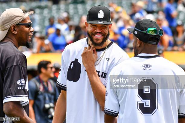 Golden State Warriors JaVale McGee jokes with Kevin Durant and Andre Iguodala during JaVale McGees JUGLIFE charity softball game on June 24 at...