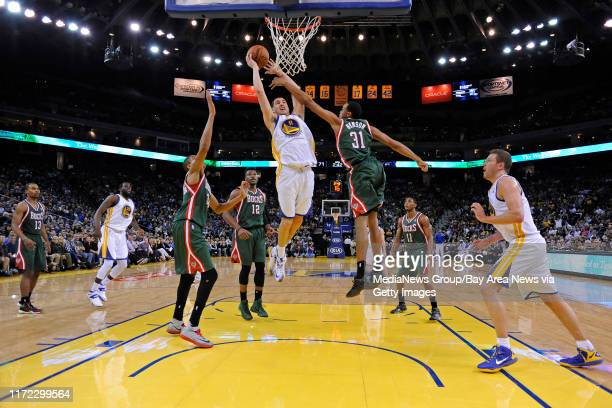 Golden State Warriors' Klay Thompson goes up for a lay up as Milwaukee Bucks' John Henson attempts to guard him in the third quarter of their game at...