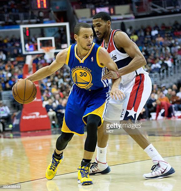 Golden State Warriors point guard Stephen Curry is defended by Washington Wizards shooting guard Garrett Temple during the first half of their game...