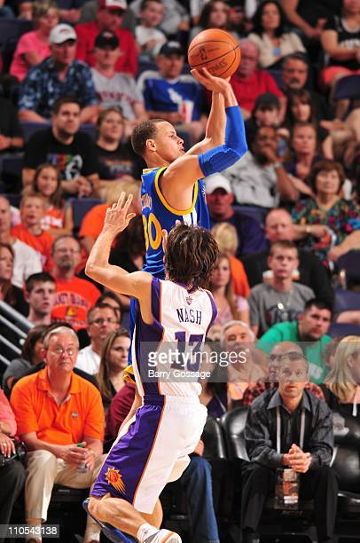 Golden State Warriors point guard Stephen Curry shoots the ball under pressure during the game against the Phoenix Suns March 18 2011 at US Airways...