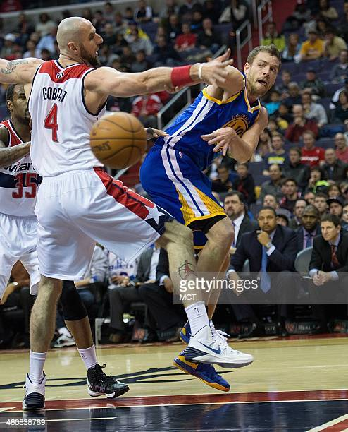 Golden State Warriors power forward David Lee passes the ball around Washington Wizards center Marcin Gortat during the first half of their game...