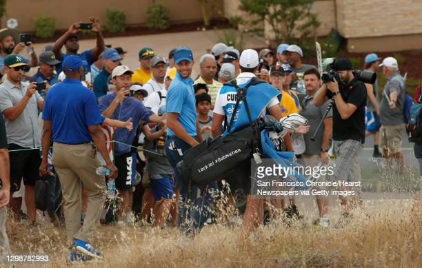Golden State Warriors star Stephen Curry makes his way to the 14th tee against a crowd of fans during the first round of the Ellie Mae Classic golf...