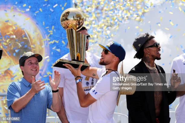 Golden State Warriors' Stephen Curry holds up the Larry O'Brien NBA Championship Trophy as majorty owner Joe Lacob applauds at the end of the...