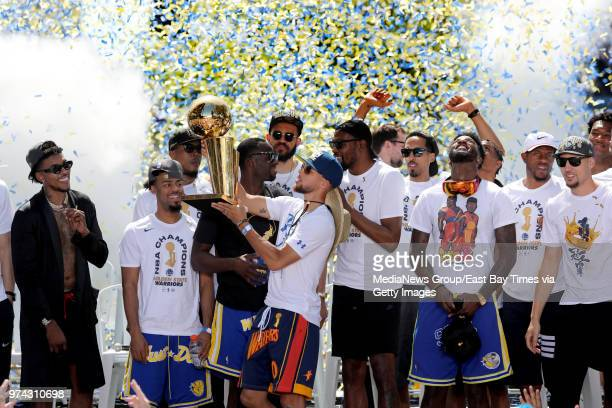 Golden State Warriors' Stephen Curry holds up the Larry O'Brien NBA Championship Trophy at the end of the Warriors championship rally followed by...