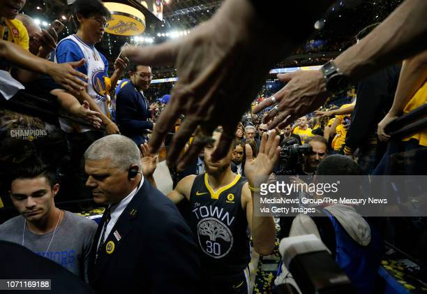 Golden State Warriors' Stephen Curry is congratulated by fans on the way to the locker room after beating the Cleveland Cavaliers 122103 in Game 2 of...