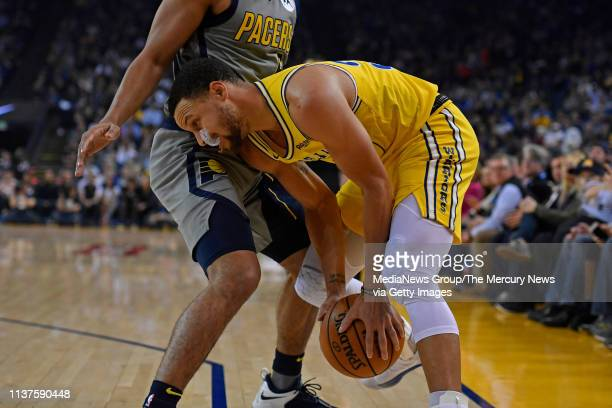 Golden State Warriors' Stephen Curry is guarded by Indiana Pacers' Cory Joseph during the first quarter of their NBA game at Oracle Arena in Oakland...