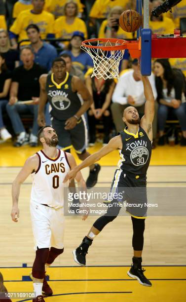 Golden State Warriors' Stephen Curry makes a layup past Cleveland Cavaliers' Kevin Love during the first quarter of Game 2 of the NBA Finals against...