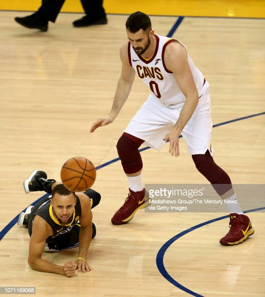 Golden State Warriors' Stephen Curry manages to pass the ball after he lost control while being guarded by Cleveland Cavaliers' Kevin Love during the...