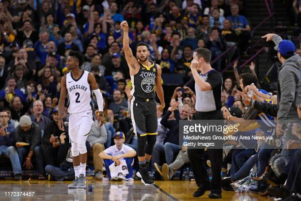 Golden State Warriors' Stephen Curry reacts after making a three-point basket past Memphis Grizzlies' Kobi Simmons during the third quarter of their...